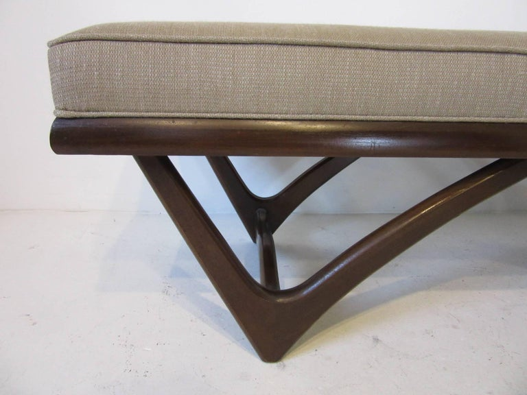 A sculptural dark ebony/walnut toned wood based upholstered bench in the manner of Adrian Pearsall . A great bench for the end of the bed , entrance way or extra lower profile seating in your living space .