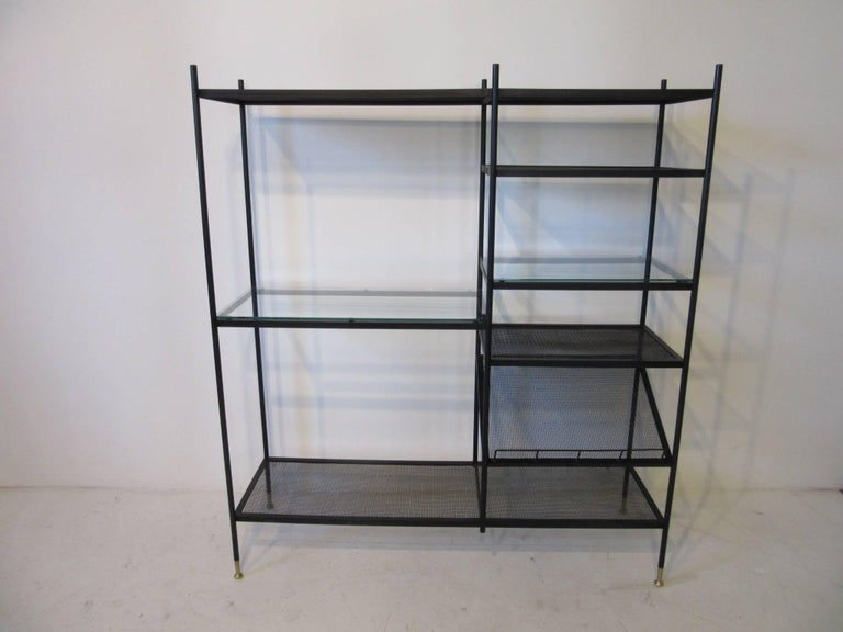 A satin black metal étagère with brass detailed leg tips and pole caps, four wire shelves , two glass shelve and a slanted book , art or magazine display shelve. Well made and could be used in a number of areas where you need something that doesn't