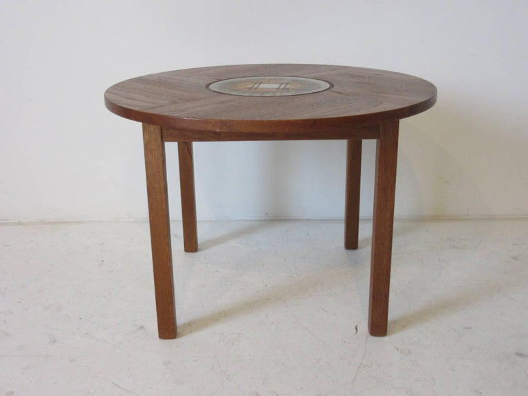 A teak wood side / end table with inlay handcrafted tile by artist and designer Tue Poulsen ink stamped to the bottom