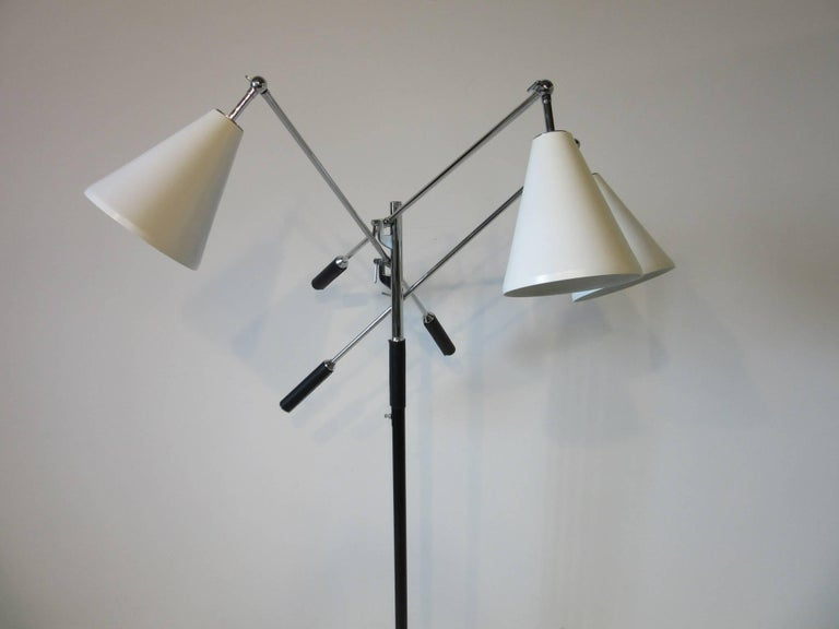 A three arm Triennale floor lamp with satin white cone shaped shades, chrome adjustable stems and staff with black leather handle covers. Having a three way light switch mounted on the pole all sitting on a round white Carrara marble base and is