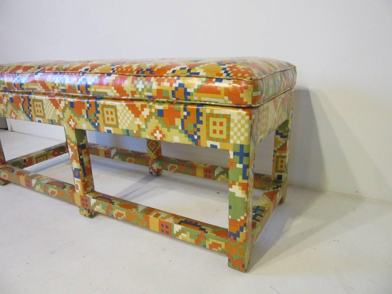 An upholstered bench with colorful, 1980s patterns in oil cloth with lower stretchers, from the period, well-crafted and perfect for that dash of color. Designed in the style of Karl Springer and Steve Chase.