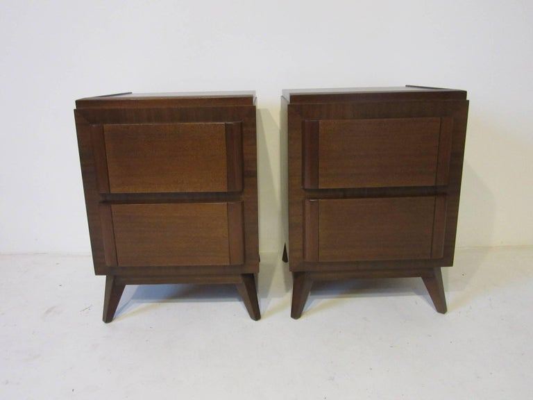 A pair of dark walnut toned nightstands with double drawers for storage and varied frontal wood grains for interest. Designed in the 1940s by famed architect and artist Eliel Saarinen father of noted furniture designer and architect Eero Saarinen.