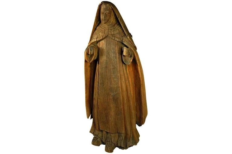 A wonderfully primitive Italian statue of Saint Anne - the mother of the Virgin Mary.  She is carved from a solid tree trunk.  Having been exposed to centuries of weather, here Saint Anne is beautifully tranquil.