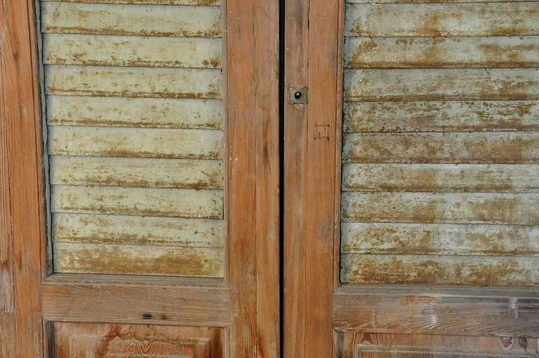 A terrific set of three washed, bleached wooden doors with painted metal louvered shutters. Wonderfully constructed with great patina. Not only fabulous built in, but would also serve beautifully as wall mounted art or headboard.