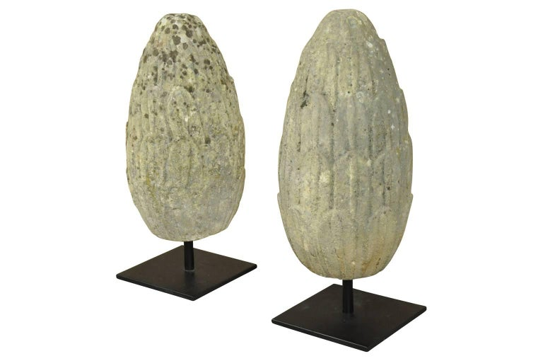 A sensational pair of mid-18th century carved stone finials, pineapples from France. These wonderful architectural elements are presented on iron stands. Terrific accent pieces for a mantel, table top or converted into lamps.