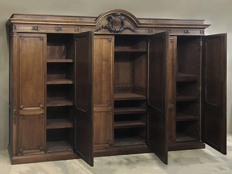 Grand 19th century French neoclassical walnut six-door armoire with bold heraldic crest measures over 13 1/2 wide, and was handcrafted in magnificent splendor from solid walnut! The panels are solid, through and through, as is of course all the