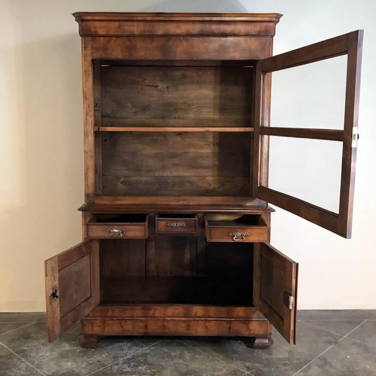 19th century Louis Philippe fruitwood bookcase was meticulously handcrafted with the tailored architecture that is the epitome of the period, all from indigenous fruitwood. The artisans carefully lined up the planks to create a pattern across the