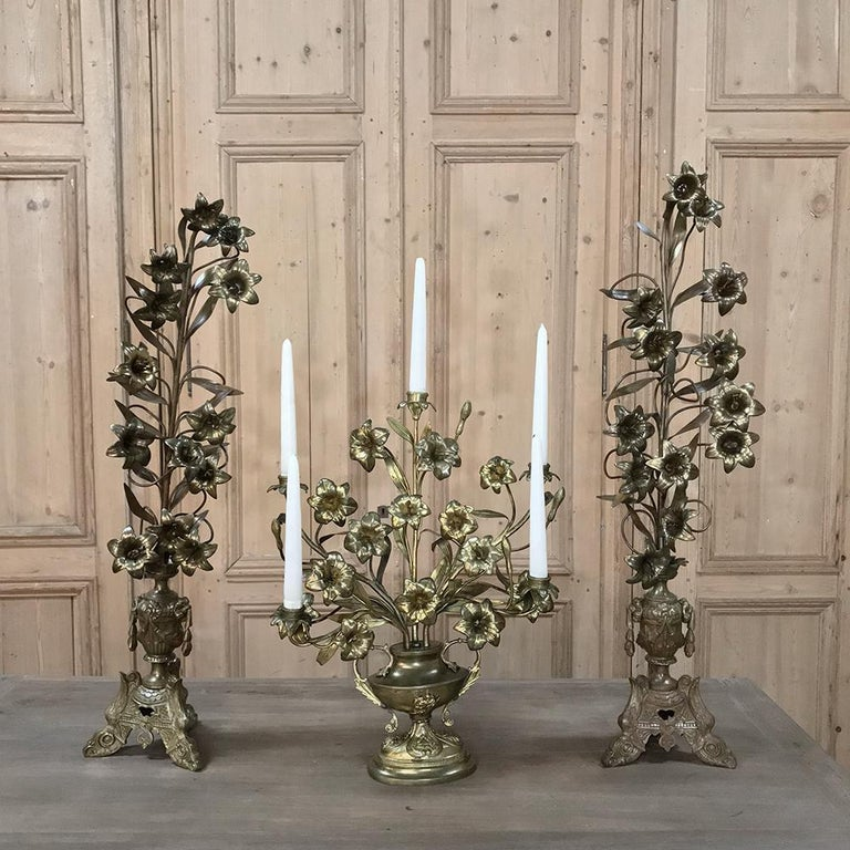19th century bronze French altar bouquet candelabra represents a masterwork of the metalsmith's art, depicting a floral bouquets of lilies set atop a classically inspired urn and base, all cast in solid bronze. Perfect for adding a timeless touch to