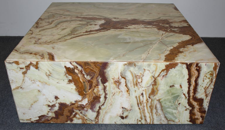 A large polished onyx coffee table with variegated rust, ocher, and onyx green tones.
