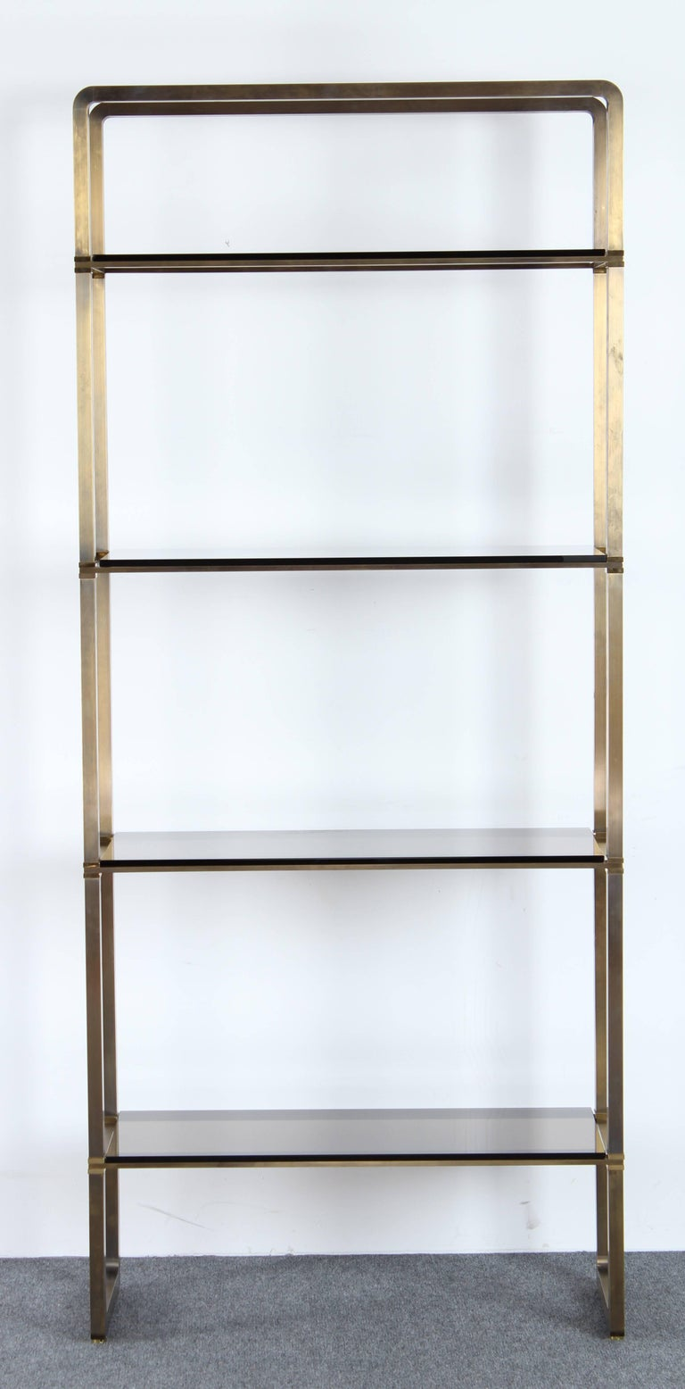 A fabulous Paul M. Jones bronze and glass four-tiered etagere or display shelf with four smoked glass shelves. Solid bronze and brass frame. Versatile and modern. Very good condition with age appropriate wear. Two shelves have minor chips, as shown