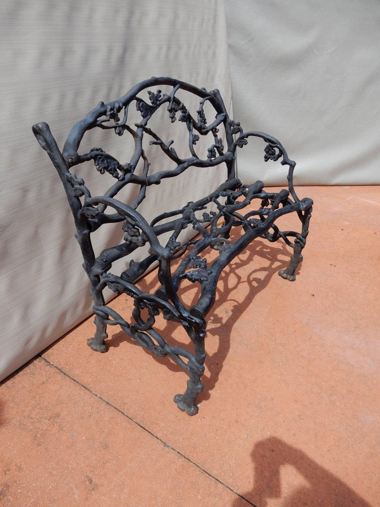 Cast iron garden bench in the naturalistic twig or Rustic pattern. Usually these Benches appear in the longer size but this bench is only 33 inches long. The bench is adorned with details of oak leaves, acorns and snakes on the arms. The Rustic or