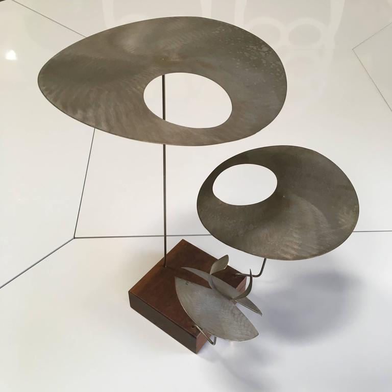 A fascinating kinetic sculpture. Biomorphic rotating metal discs cantilevered on metal rods and attached to square wooden base. Provenance accompanies.