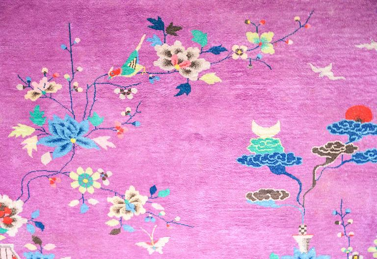 A beautiful early 20th century Chinese Art Deco rug woven with rich jewel tones including a deep amethyst purple field, surrounded by a taupe border. The central field includes an overlay of multicolored auspicious flowering chrysanthemums, peonies,