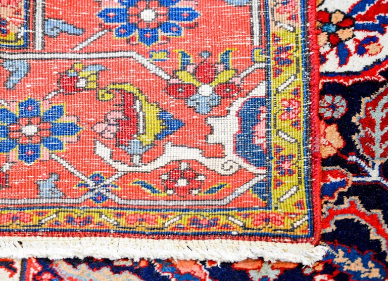 An amazing mid-20th century Persian Heriz rug with a large central multi-lobed floral medallion on a black background. The field is intensely woven with a complementary floral pattern. The border is comprised of a wide stylized floral pattern on a