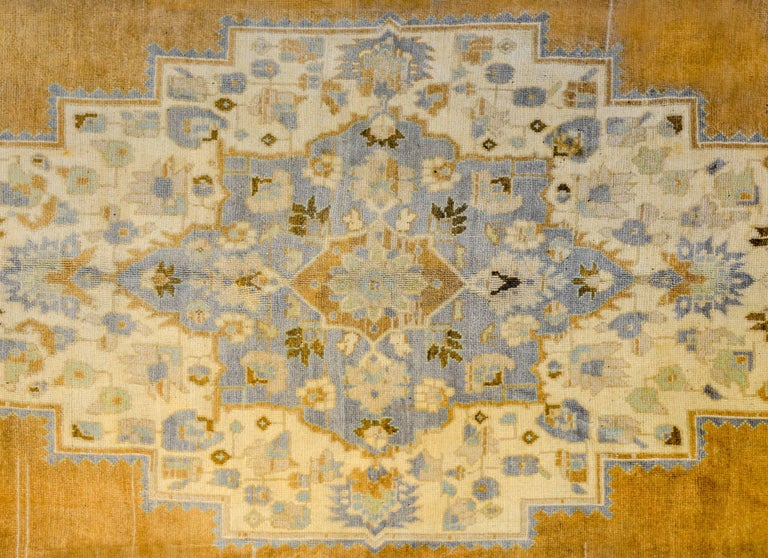 A vintage Turkish Oushak rug with a beautiful diamond medallion amidst a field of flowers woven in gold, indigo, brown, and cream color wool. The border is exceptional, with large-scale wide stylized floral and leaf pattern flanked by different