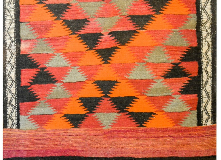 A fantastic vintage Afghani Kilim rug with a bold all-over diamond pattern with crimson, orange, black, and green diamonds. The ends are composed of three wide colored stripes, with a fringe end.