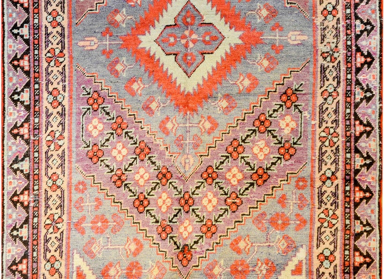 An early 20th century Central Asian Samarkand rug with large diamond and floral medallion, amidst a field of flowers, surrounded by a complementary floral border, all woven in crimson, lavender, indigo, and gold vegetable dyed colored wool.