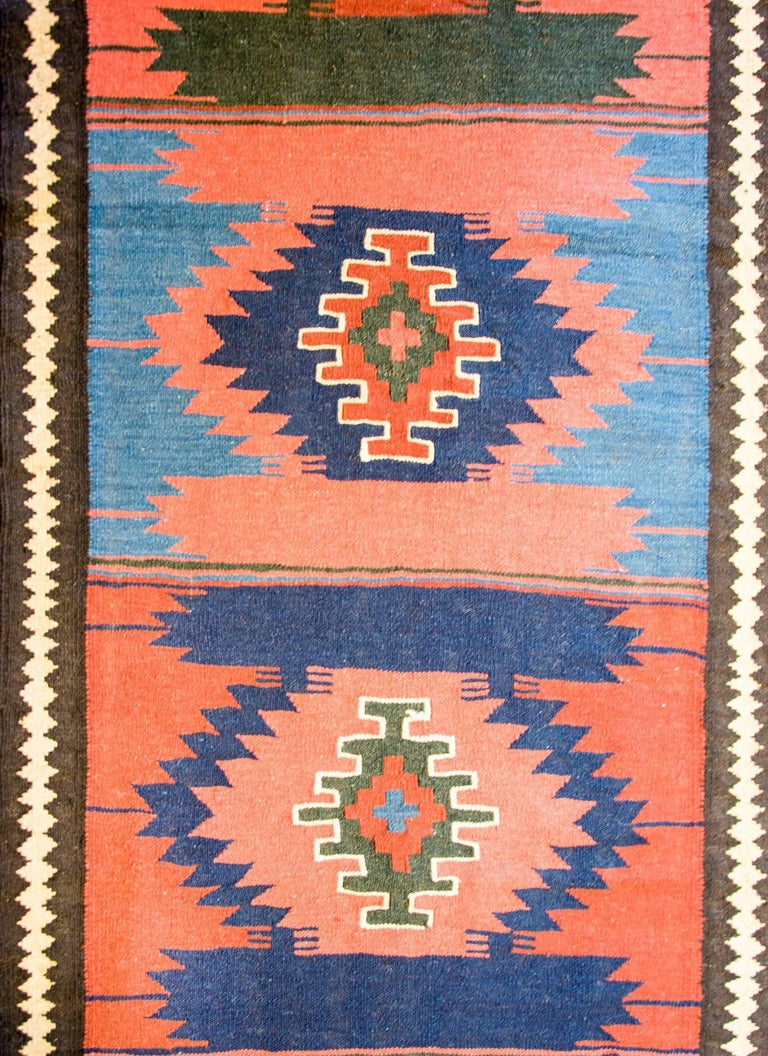 An early 20th century antique Persian Bakhtiari runner with ten diamond medallions woven in crimson, salmon, indigo, and green surrounded by a simple harlequin striped border.