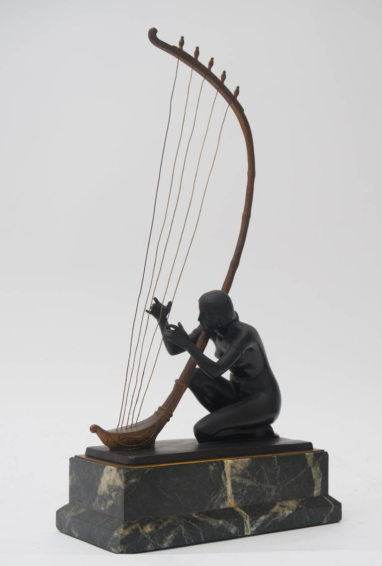 This piece was acquired from a Palm Beach collection and is by the Austrian sculptor Hans Muller. Here Muller has captured a nude maiden playing a stringed instrument as to beckon us with an alluring sound and memories.  This piece has tones of