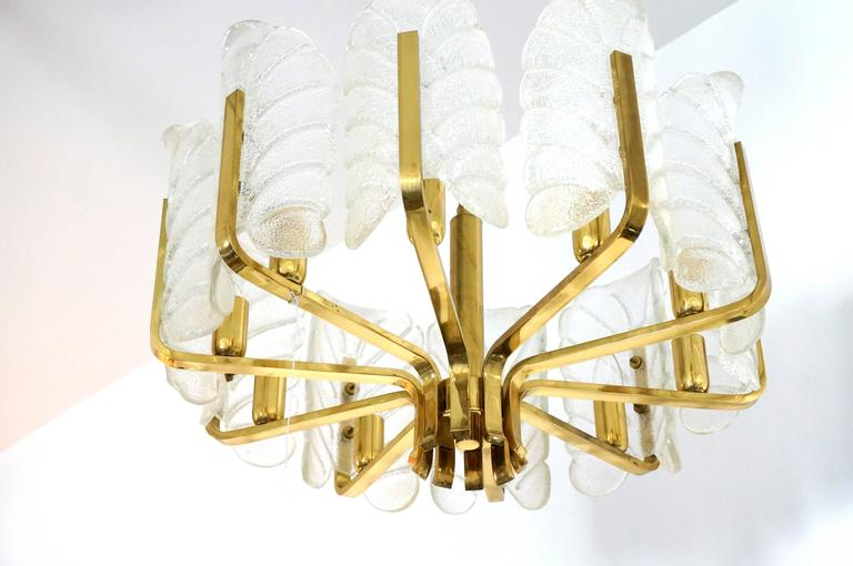 This Hollywood-Regency style chandelier was produced in the 1960s by the iconic firm of Oreffors and designed by Carl Fagerlund.  The ten stylized glass-leaf shades are in a molten clear and white coloration.  The piece has a great movement to it