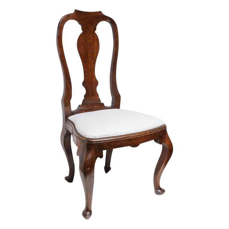 This set of four Queen Anne revival dining side chairs date from the mid to late 19th century. The frames look to be in walnut and are hand-carved with cabriolet leg, serpentine back and serpentine shaped seat. The slip seat is easily removed to
