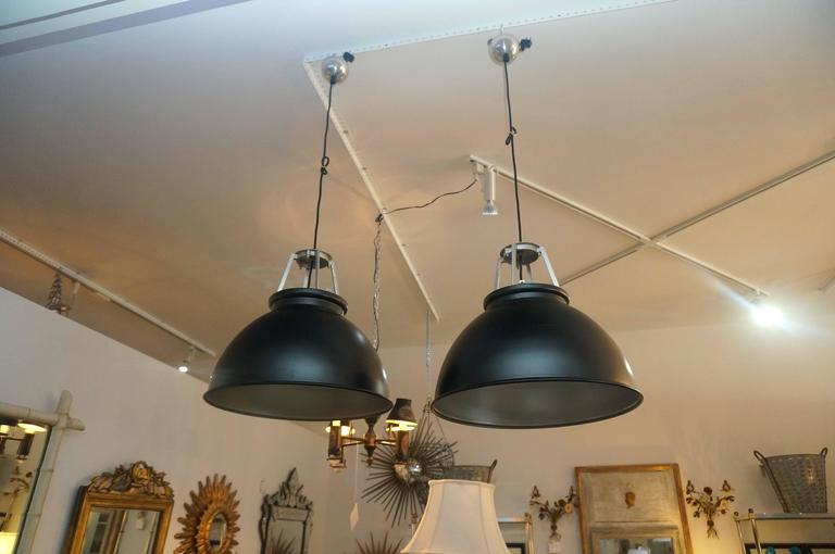 This pair of 1940s industrial style light fixtures were purchased in London (originated in France) and have been professionally restored with new wiring and paint. The exterior is a dark black with soft-silver/aluminum painted accents.