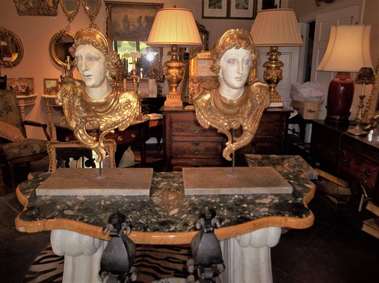 Possibly angels from an altar (note the feathers) or the usual cherubs or putti. Probably early 19th century, Italy or France.   Crisply carved with gilt highlights. On iron rods and heavy marble bases. Cannot tip over, very sturdy. Can be wall hung