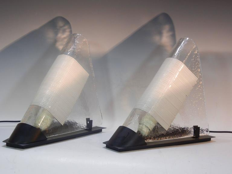 This pair of bedside table lamps is composed of folded and textured clear glass panels with rows of white glass-rod inclusions. The two lamps sit on triangular black metal bases and have electrical cords emanating from the open ends.  These
