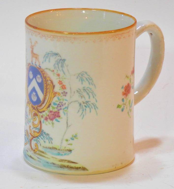 This hand-painted famille-rose and gold porcelain tankard has a Western armorial shield with three scallop shells of Saint-James around a white chevron on a blue field beneath a stag. The shield is mounted on and held erect by an elaborate gold