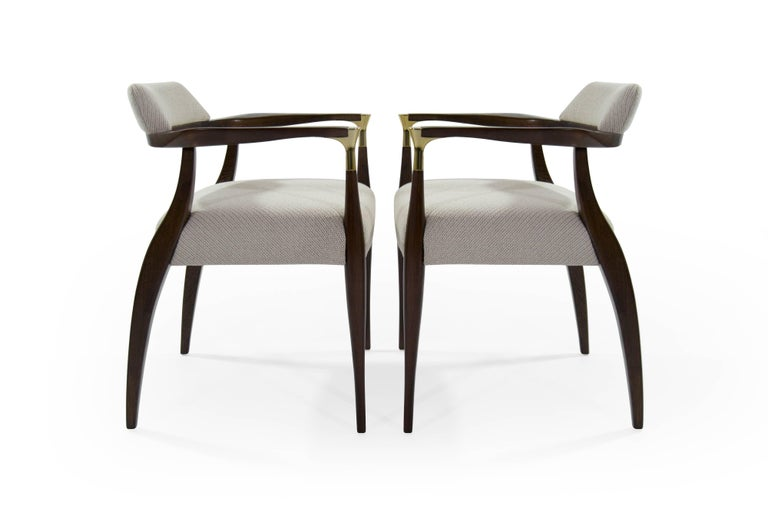 A rare pair of Scandinavian modern armchairs in the style of Ib Kofod-Larsen, Denmark, circa 1950s.  This set features newly polished brass arm-tip details. Newly upholstered in an off-white coda wool by Maharam/Kvadrat. Sculptural walnut frames