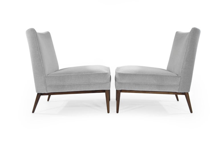 Pair of slipper chairs by Paul McCobb for Directional, circa 1950s.  Newly upholstered in grey mohair, walnut bases fully restored.
