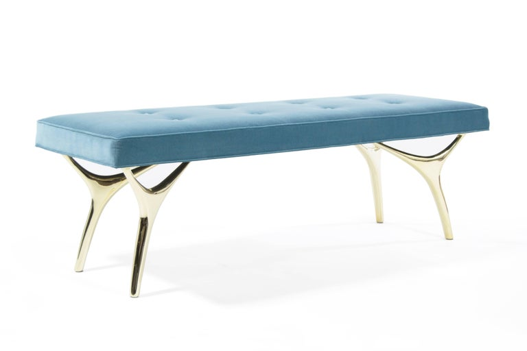 The Crescent Bench floats effortlessly, poised on brass fingertips. Inspired by 20th century visionaries like Vladimir Kagan and Gio Ponti, this bench offers a unique perspective. The plush bench cushion is shown in light blue velvet upholstery to