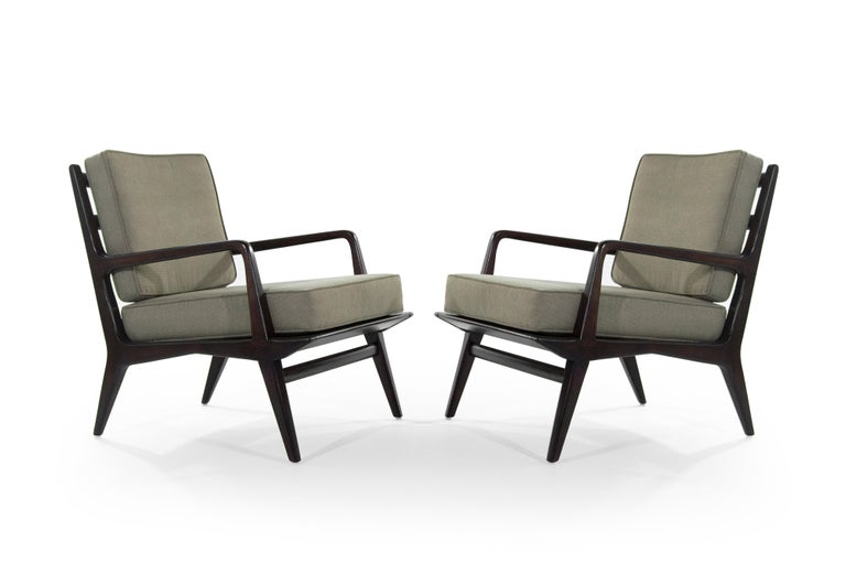 Pair of lounge chairs featuring sculptural walnut frames in a deep brown finish, designed by Carlo di Carli for M. Singer & Sons, American, 1950s. Wood fully restored, newly upholstered.