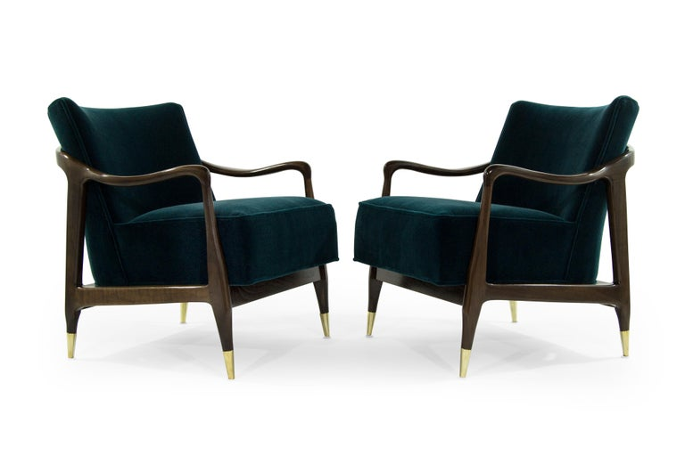 Exquisite pair of Mid-Century Modern lounge chairs featuring sculptural walnut frames, which have been expertly restored to their original integrity. They boast handcut high grade foam, as well as hand polished brass sabots. They have been recovered