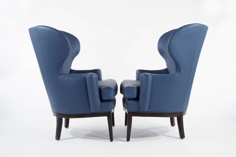 Extremely rare pair of early wingback chairs designed by Edward Wormley for Dunbar, circa 1940s. Newly upholstered in blue Spinneybeck, walnut bases fully restored.