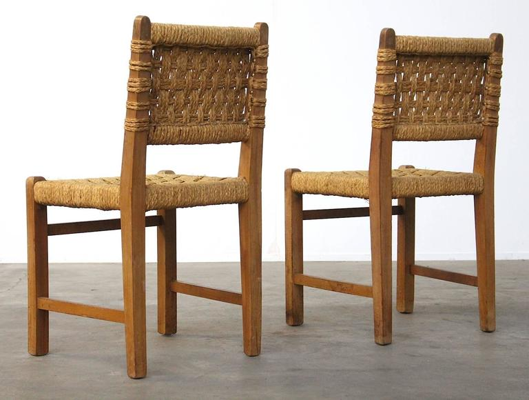 A stunning pair of oakwood and rope/ sisal side chairs by the designer couple Adrien Audoux and Frida Minet; manufactured in the 1950s in Marseille, France. Beautiful minimalistic design with lots of similarities and suggestions to the work of