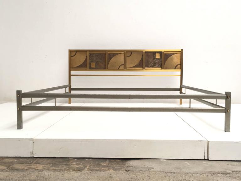 Beautiful bed by italian sculptor and artist, Luciano Frigerio, this bed was produced circa 1970 and features a stunning six-panel, sculptural relief headboard finished in cast bronze and brass, complete with original bed frame finshed in chromed