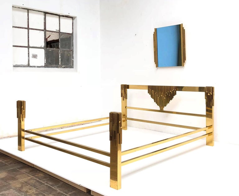 Extraordinary and super rare italian brass bed in the style of Osvaldo Borsani with matching sculptural motif blue glass mirror from circa 1960. This is one of the most exquisite beds I have seen in a very long time . Both the headboard and legs