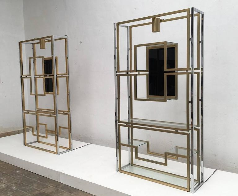 Supremely elegant pair of illuminated vitrine or étagère by Kim Moltzer with a beautiful sculptural geometric form, finished in brass and chrome, which support eight glass display shelves and a further central display niche that features a