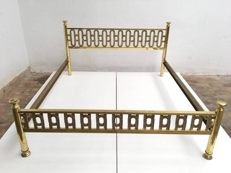 Beautifully crafted brass double bed by Italian artist Luciano Frigerio. The headboard and foot rail feature a wonderful heavy brass sculptural form interlocking loop motif with incised detailing in excellent condition The two side rails are
