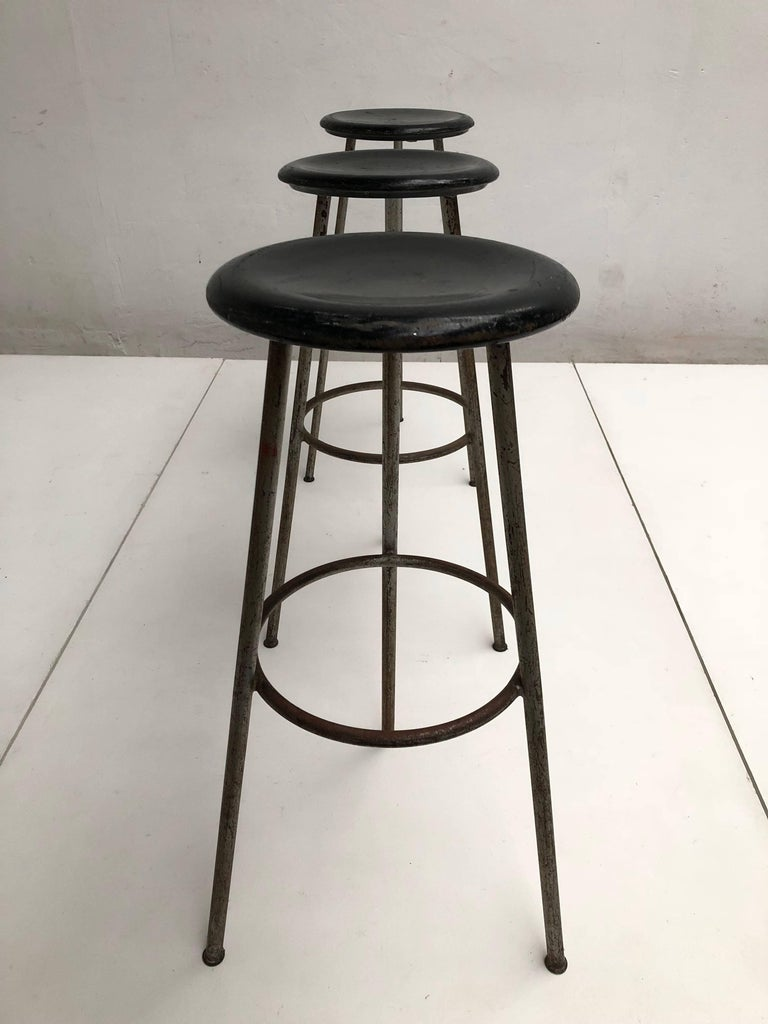 Unique set of three high tripod working / bar stools that originated from a Swiss confection Atelier   Carved black lacquered wooden round seating on tripod tubular steel grey enamelled legs  All stools have a lovely old and aged patina from