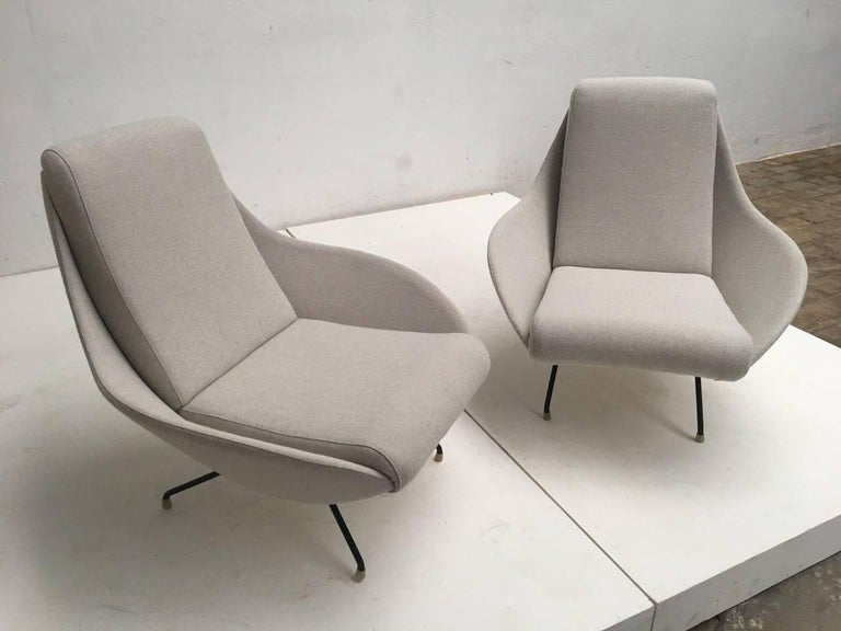 Pair of exquisite sculptural form Italian lounge chairs from the early-mid-1950s period featuring dramatic flowing eliptical 'mantis' form wings with a subtle sculptural double curvature which envelope you and form an integral lateral and arm