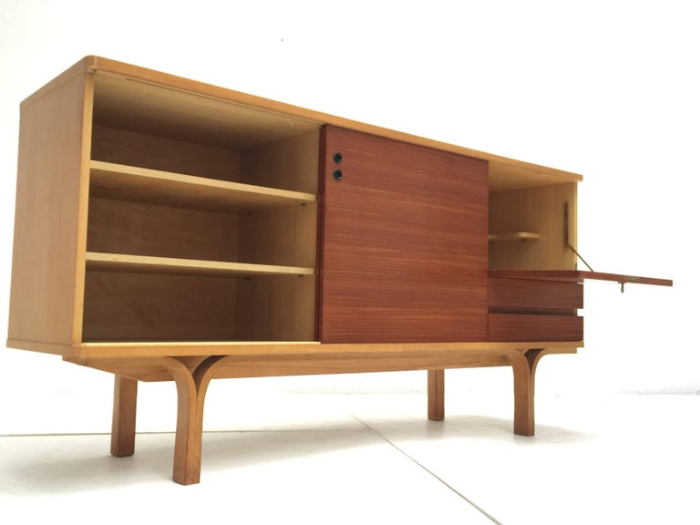 Rare and supremely elegant, ash and mahogany wood, credenza bar designed by Joseph Andre Motte in 1954 for 'Group 4, Charron,' France; complete with the extremely rare original decorative brass key for the lockable bar compartment.   The surrounding