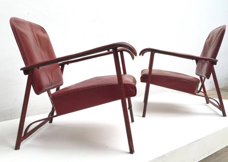 Supremely elegant pair of Jacques Adnet lounge chairs requiring restoration, the pair are currently finished in their original hand-stitched leather complete with original patinated brass hardware (please see image 6).