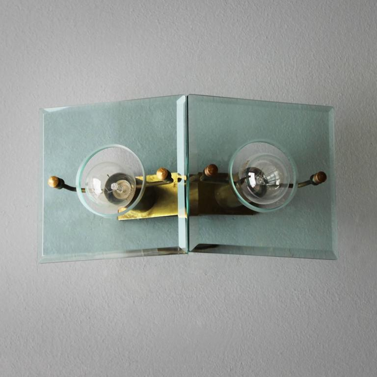 A brass and cut-glass wall light by Arredoluce, Italy.  Dimensions: Depth 4.5 in. (11.5 cm), width 10.4 in. (26,5 cm), height 5.5 inches (14 cm). The electricity is used but in a good condition, approved to European standards. Works in the US. Small
