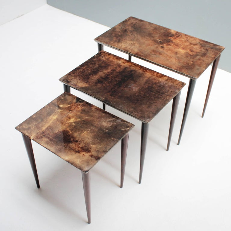 Set of three Aldo Tura nesting tables in lacquered goatskin and mahogany. This particular set was executed, circa 1960 in a somewhat austere style, but - as strong contrast - is covered with a rich brown tanned parchment. Dimensions: Height: 16.1