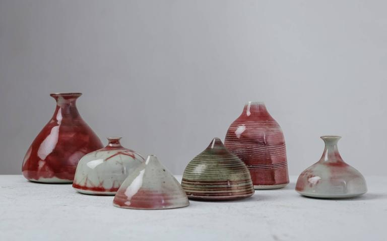 A set of six small vases with a white a mostly red and white glaze finish, by French ceramist Franco Agnese. The lowest piece is 5.5 cm (2.2 inch) high and has 8 cm (3 inch) diameter. The tallest vase is 12.5 cm (5 inch) with a 12 cm (4.7 inch)
