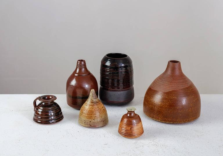 A set of six vases in a brown to nearly black glaze finish, by French ceramist Franco Agnese.  The lowest piece is 7.5 cm (3 inch) high and has a 6 cm (2.4 inch) diameter. The tallest vase is 15.5 cm (6.1 inch) high with a 16 cm (6.3 inch)