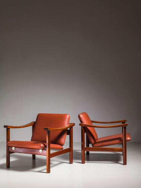 A pair of rare Hans Wegner lounge chairs for GETAMA. The chairs are made of a wooden frame, with a reclining seat and backrest, supported by metal rails. The chairs were professionally reupholstered in our atelier with a beautiful brown leather. *