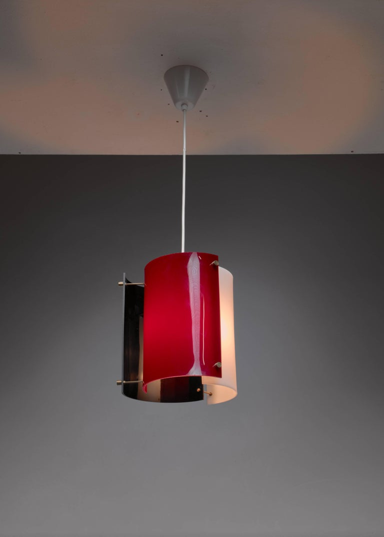 A Yki Nummi 1960s pendant for Orno. The lamp is made of three semicircular plexiglass elements in white, black and purple, held together with thin brass rods. The colored plexiglass creates a beautiful, atmospheric light. A variation with a peach,